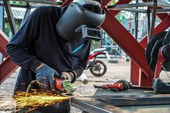 Craftsman sawing metal sparkles all around workshop. Working at noon.  stock images