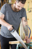 Craftsman sawing wood with hand saw in workshop Stock Photography
