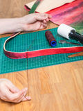 Craftsman sews new belt for leather bag Royalty Free Stock Image