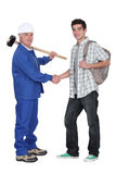 Craftsman shaking hands with apprentice Royalty Free Stock Photos