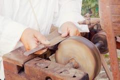 Craftsman sharpens an old knife on a wheel of an antique grinder Stock Image
