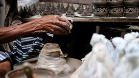 Craftsman shaving the lid of clay pot for perfect shape. For selling stock video