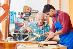 Craftsman shows apprentice how to work Royalty Free Stock Photos