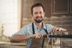 Craftsman smiling with the project he is busy making Royalty Free Stock Photos