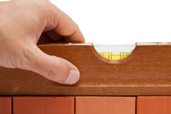 Craftsman with spirit level. Craftsman measuring a brick wall with a spirit level royalty free stock photography