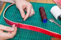 Craftsman stitches new leather belt Stock Photo