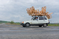 Craftsman transports wicker-work on a roof of a small car Royalty Free Stock Photos