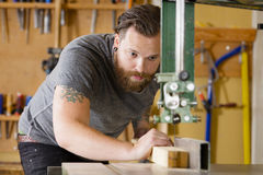 Craftsman using band saw for splitting wood plank in workshop Stock Photos