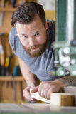 Craftsman using bandsaw for splitting wood plank in workshop Royalty Free Stock Photo