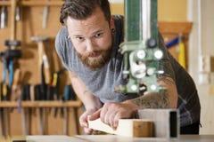 Craftsman using bandsaw for splitting wood plank in workshop Stock Image