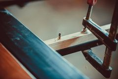 Craftsman using clamps fixate two pieces of wood and iron. The process of making desk, furniture Royalty Free Stock Photography