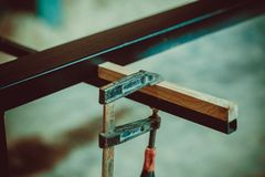 Craftsman using clamps fixate two pieces of wood and iron. The process of making desk, furniture Royalty Free Stock Image