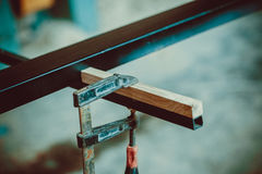 Craftsman using clamps fixate two pieces of wood and iron. The process of making desk, furniture Royalty Free Stock Photo