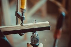 Craftsman using clamps fixate two pieces of wood and iron. Man using the drill makes a hole in wood and iron strap. The process of making desk, furniture Royalty Free Stock Image