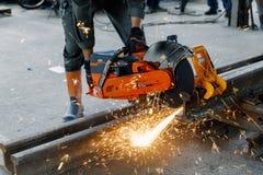 Craftsman using machines cutting steel rail.  Royalty Free Stock Images