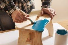 Craftsman varnishing and handmade stool Royalty Free Stock Photography