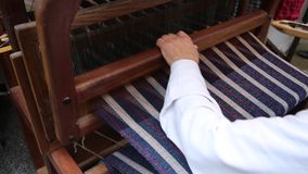 Craftsman weaves a fabric with an ancient hand loom stock video