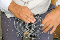 Craftsman weaves wire vase with hands Stock Photos