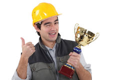 Craftsman winking holding trophy Royalty Free Stock Images