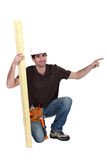 Craftsman with wood. Craftsman kneeling with plank of wood Stock Photo