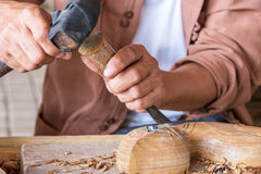 Craftsman wood carving. Hands of the craftsman wood carving a bas-relief royalty free stock photos