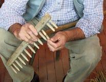 Craftsman of wood while repairs an old wooden rake Royalty Free Stock Photos