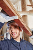 Craftsman with wood smiling. And learning during apprenticeship Stock Images