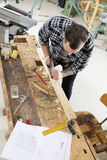 Craftsman work with plane on wood plank in workshop Stock Photo