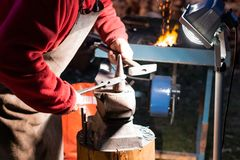 A craftsman working with fire and a hammer on a glowing iron. middle age, flame, metal, handmade; stock image