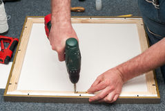 Craftsman working on frame in frame shop. Professional framer hand holding frame angle. Top view. Copy space Stock Images