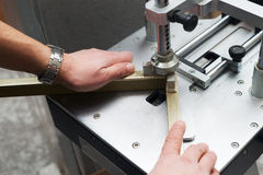 Craftsman working on frame in frameshop. Professional framer hand holding frame angle. Top view stock images