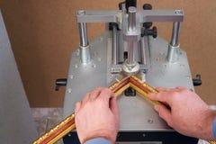 Craftsman working on frame in frameshop. Professional framer hand holding frame angle. Top view Stock Image