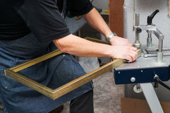 Craftsman working on frame in frameshop. Professional framer hand holding frame angle. Top view Royalty Free Stock Photography