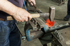 A craftsman working with a hammer and anvil Royalty Free Stock Photo