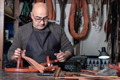 Craftsman working the leather in his small saddlery workshop royalty free stock images