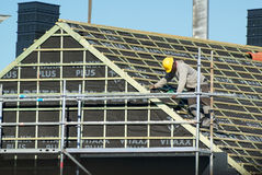 Craftsman working on a roof. Pepingen, Belgium - September 30, 2015: Craftsman working on a roof. He wears a yellow safety protection helmet royalty free stock photos