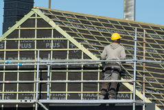 Craftsman working on a roof from a scaffold. Pepingen, Belgium - September 30, 2015: Craftsman working on a roof from a scaffold. He wears a yellow protection Stock Photo