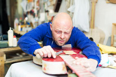 Craftsman working with unfinished guitar Royalty Free Stock Photography