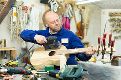 Craftsman working with unfinished guitar Stock Photos