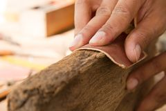 Craftsman working use sandpaper sanding plank wood. Craftsman use sandpaper sanding plank wood for design house furniture, close up Royalty Free Stock Photos