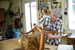 Craftsman working on wooden armchair Royalty Free Stock Photo