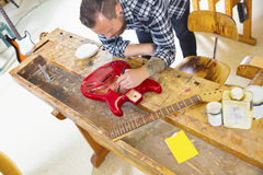 Craftsman working at workshop with a guitar Royalty Free Stock Images