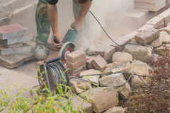 Craftsman works with an electric grinding machine Royalty Free Stock Images