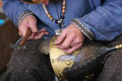 Craftsmans delicate touch. A craftsman making a medieval soldiers helmet the oldfashioned way Royalty Free Stock Image