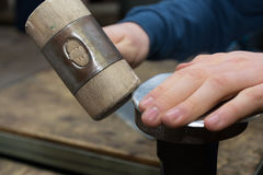 Craftsmen bend plate with mallet Stock Image
