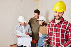 Craftsmen group as a team. Planning with architectural drawing stock images