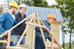 Craftsmen making new building. In cooperation with carpenter stock photos