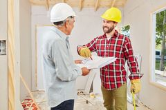 Craftsmen renovating and planning new building. At construction site stock photos