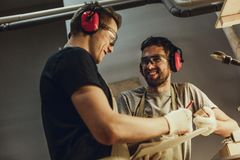 Craftsmen smiling and making sketches together royalty free stock photos