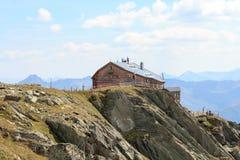 Craftsmen standing on the roof of alpine hut Bonn Matreier Hutte, Hohe Tauern alps, Austria Stock Photo